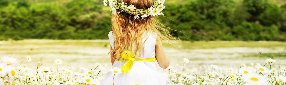 little girl in a meadow surrounded with flowers